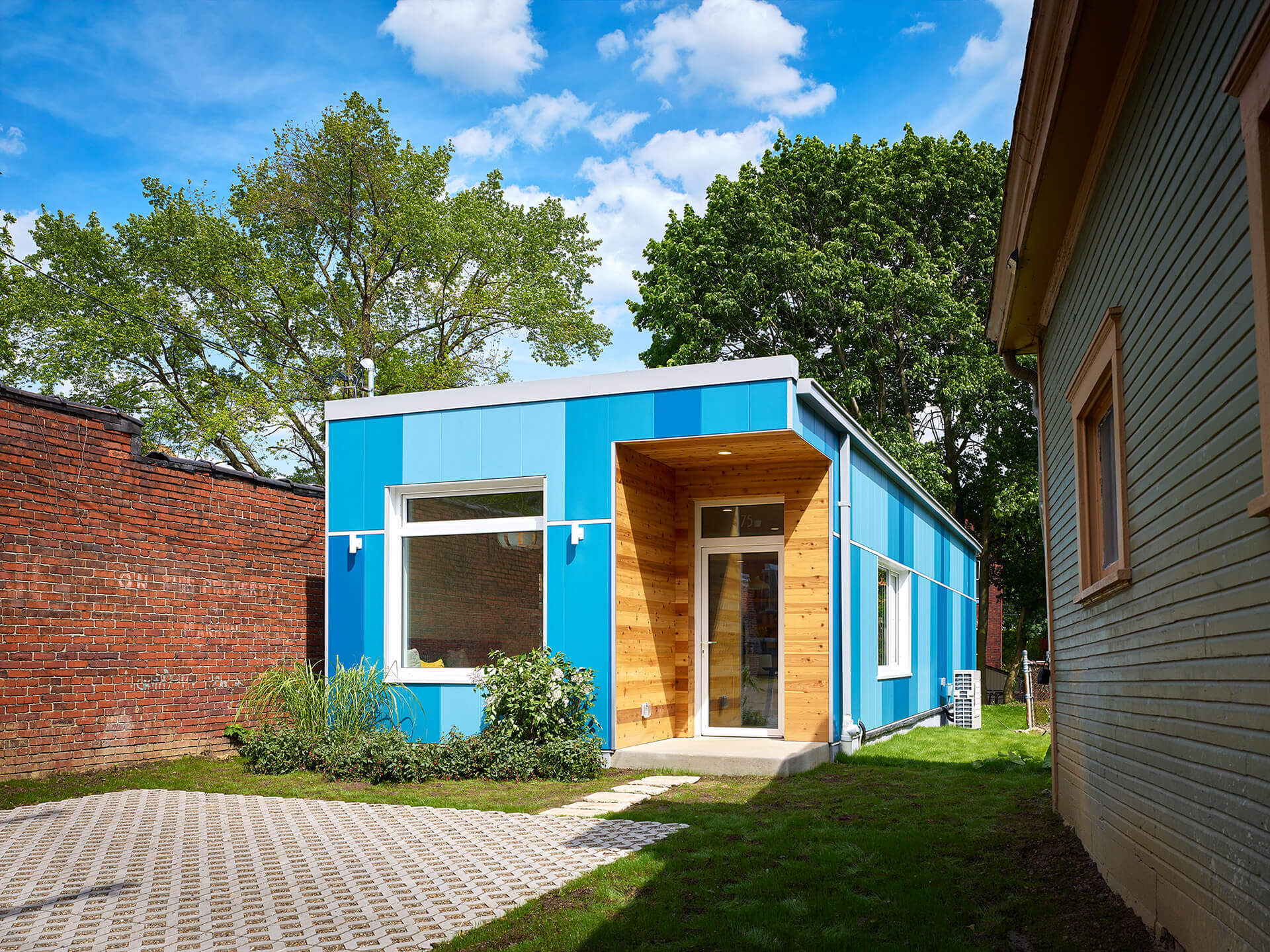 Small modular home with vertical blue custom color Illumination panels in a variety of shades