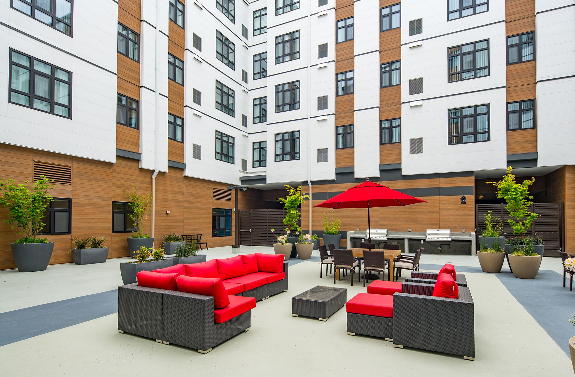 Courtyard of Thai Binh apartments with red sofa and umbrella