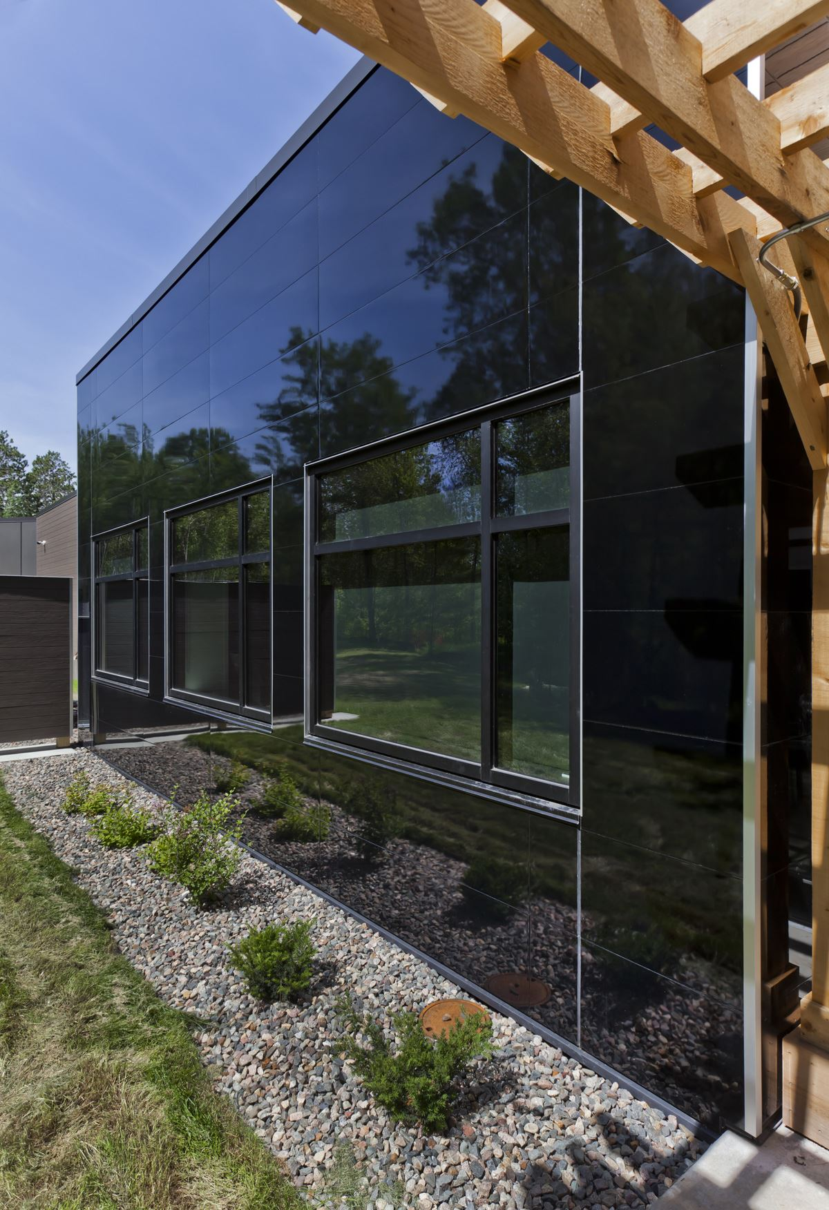Side of Paul Bunyan building with Miraia panels in Onyx showing reflection of trees